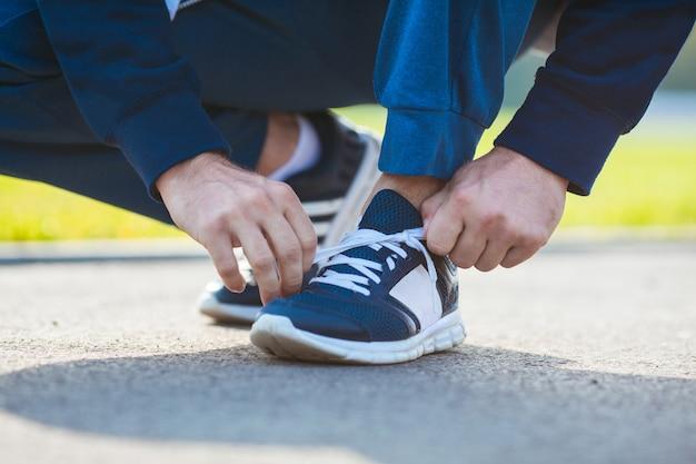 Un homme attachant ses lacets avant de commencer l'entraînement