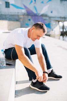 Homme attachant ses lacets de chaussure droite