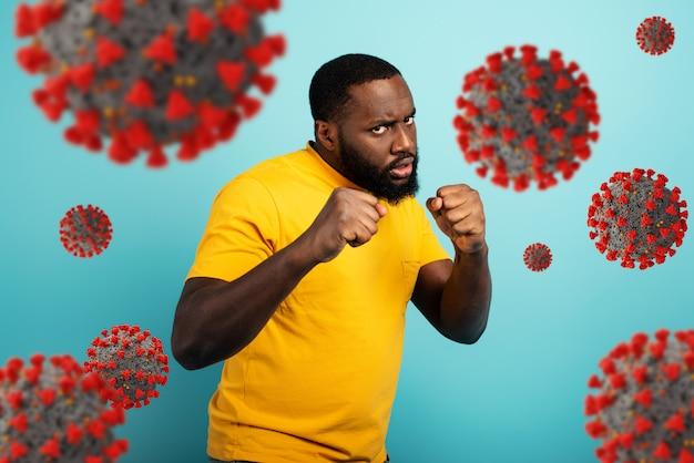 Un homme attaque d'un coup de poing le coronavirus covid19. fond bleu