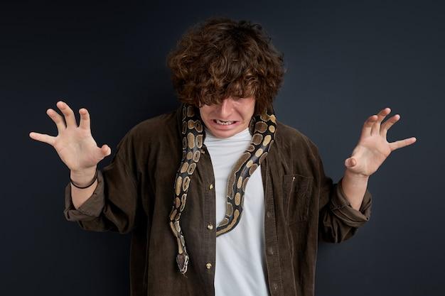 L'homme a une attaque de panique ayant un serpent sur ses épaules, un gars confus ne peut pas bouger, fait une grimace par peur