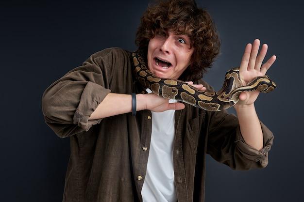 L'homme a une attaque de panique ayant un serpent sur ses épaules, un gars confus ne peut pas bouger, fait la grimace par la peur
