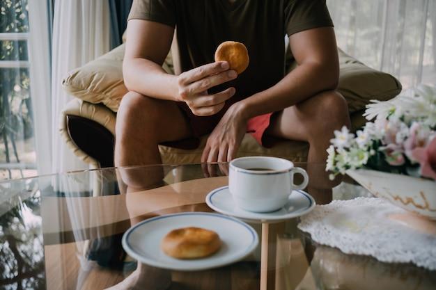 Homme atteignant pour attraper des biscuits et du café.