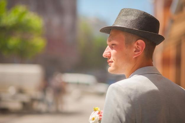 Un homme attend une femme à une date. le gars au chapeau bohème regarde vers la rue.