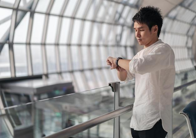 Homme en attente de vol et regardant la montre intelligente à l'aéroport
