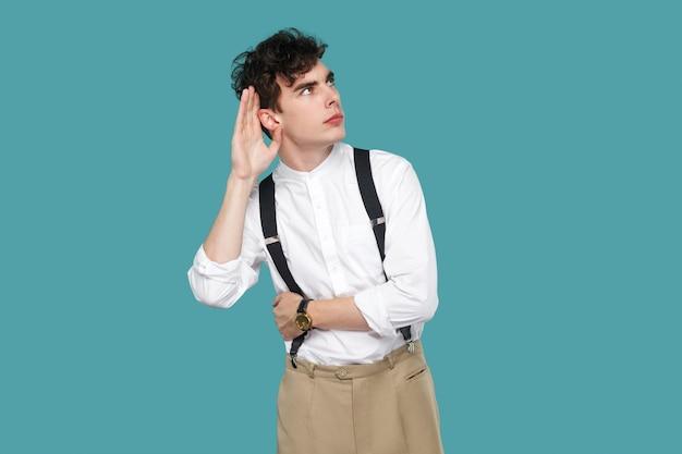 Homme attentif essayant d'entendre avec la main près des oreilles. portrait de beau jeune homme d'affaires bouclé hipster en chemise blanche décontractée classique, jarretelle debout. tourné en studio intérieur isolé sur fond bleu