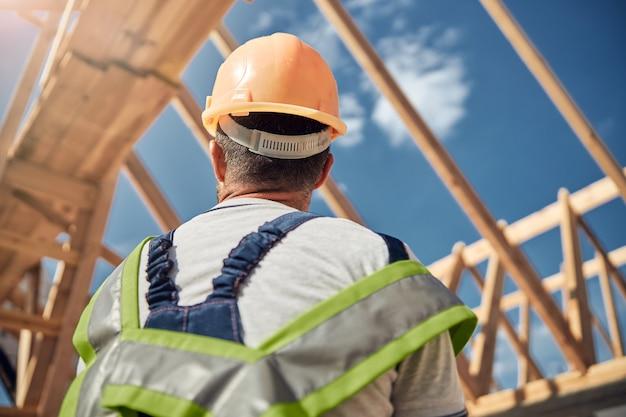 Homme attentif portant un casque au travail, préparant des poutres pour la fabrication du toit