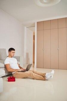 Homme attirant concentré tapant sur son ordinateur portable