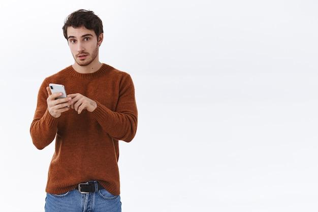 L'homme attire l'attention tout en utilisant un téléphone portable, vous regarde faire une commande de livraison en ligne avec une application pour smartphone