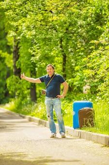 L'homme attrape une voiture qui passe par une journée ensoleillée