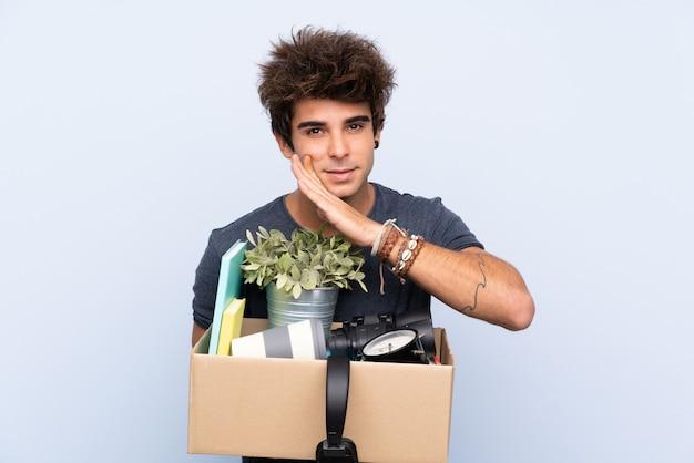 Homme attraper une boîte pleine de choses sur un mur isolé