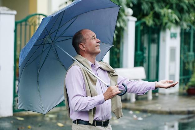 Homme attraper des gouttes de pluie
