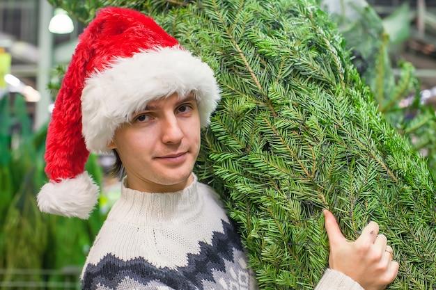 Homme au bonnet de noel achetant un arbre de noël et et montrant les pouces vers le haut