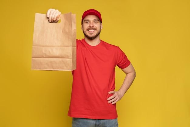 Homme au bonnet rouge, t-shirt donnant l'ordre de restauration rapide isolé sur mur jaune