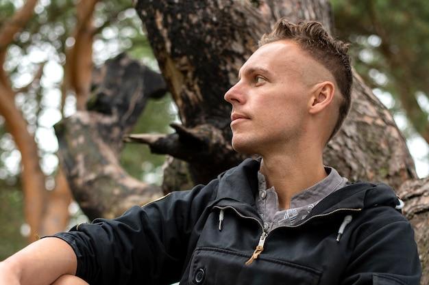 Un homme au bord d'un lac, assis sur les racines d'un arbre. pour n'importe quel but.