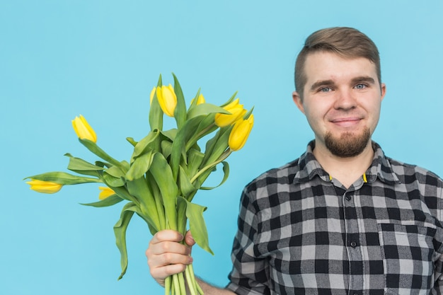 Homme au bouquet de tulipes jaunes. tulipes jaunes entre les mains d'un homme barbu sur fond bleu