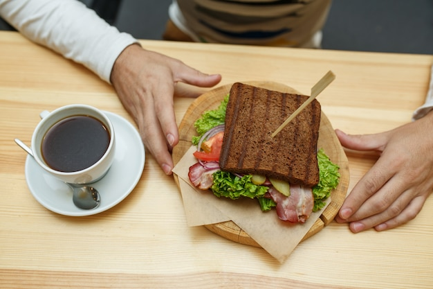 Homme au café prendre sa commande de sandwich et café