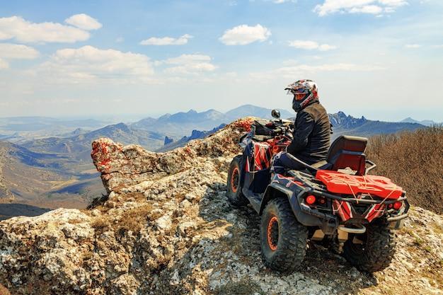 Homme au casque assis sur un quad vtt dans les montagnes