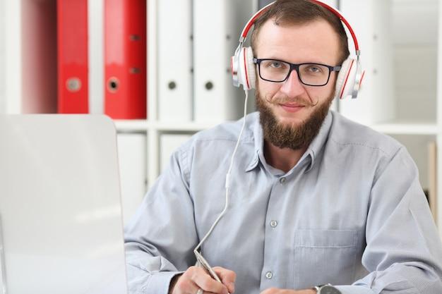 Un homme au casque écoute de la musique et apprend en ligne. prend des notes dans un cahier et regarde la caméra