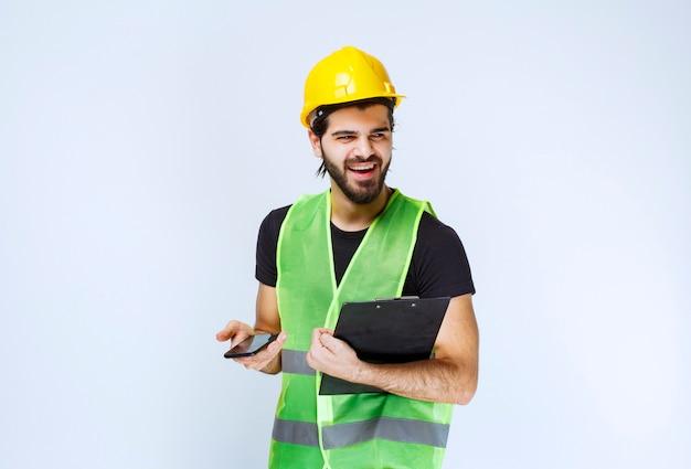 Homme au casque jaune tenant un dossier de projet et un smartphone.