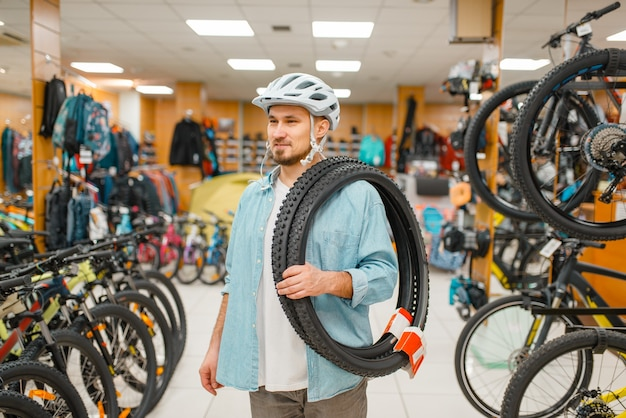 L'homme au casque de vélo détient des pneus de vélo, faire du shopping dans un magasin de sport. mode de vie extrême de la saison estivale, magasin de loisirs actifs, clients achetant du matériel de vélo