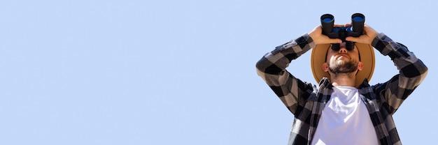 L'homme au chapeau et une chemise à carreaux gris regarde à travers des jumelles sur un fond bleu. bannière.