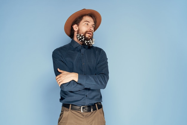 Homme au chapeau de fleurs dans le mur bleu de style écologie émotions barbe.