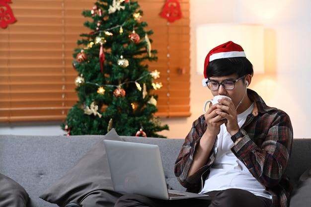 Homme au chapeau de père noël buvant une boisson chaude et naviguant sur internet avec un ordinateur portable dans le salon.