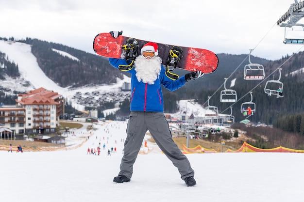 Homme au chapeau de père noël avec un snowboard dans une station de ski.