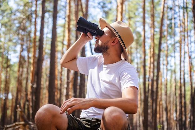 L'homme au chapeau regarde à travers des jumelles lors d'un voyage de camping. randonnée en montagne, forêt.