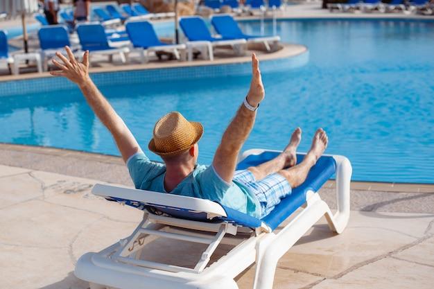 Homme au chapeau se faire bronzer sur un transat au bord de la piscine