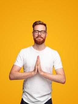 Homme au gingembre méditant avec les mains de prière