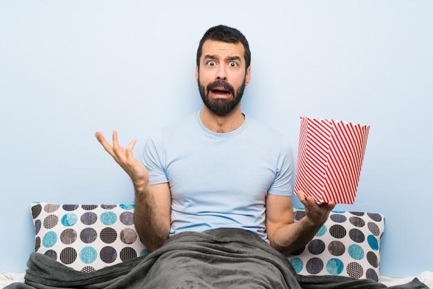 Homme au lit avec barbe mangeant des popcorns