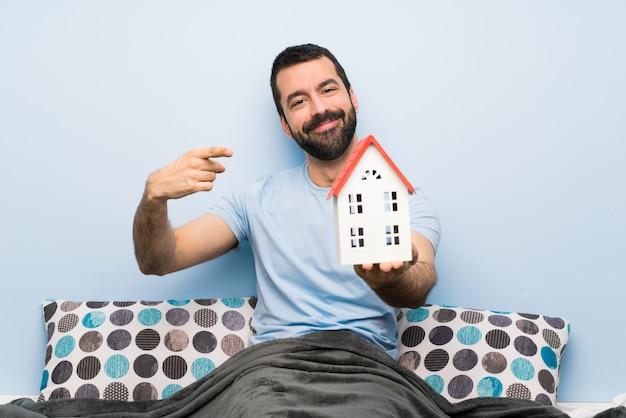 Homme au lit avec barbe tenant une petite maison