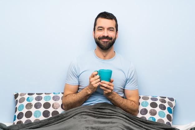 Homme au lit avec barbe tenant une tasse de café