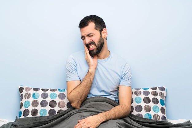 Homme au lit avec maux de dents