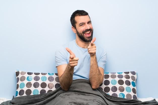 Homme au lit pointant vers l'avant et souriant