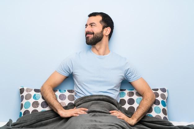 Homme au lit posant avec les bras à la hanche et souriant