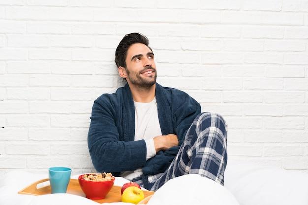 Homme au lit avec robe de chambre et petit déjeuner en levant en souriant
