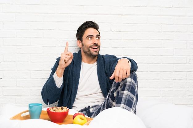 Homme au lit avec une robe de chambre et prenant son petit déjeuner avec l'intention de réaliser la solution tout en levant un doigt
