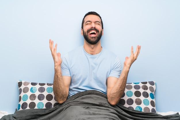 Homme au lit souriant beaucoup