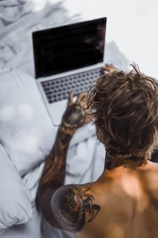 Un homme au lit travaillant sur un ordinateur portable, vérifiant le courrier, regardant un film, écoutant de la musique