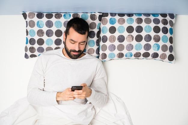 Homme au lit en vue de dessus, envoyant un message avec le téléphone portable