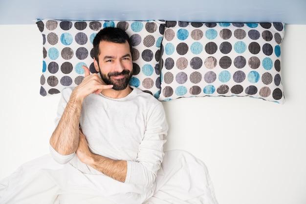 Homme au lit en vue de dessus en faisant un geste de téléphone