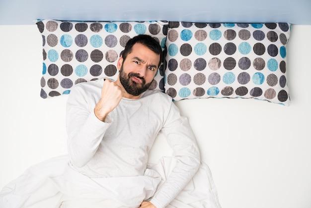 Homme au lit en vue de dessus avec un geste en colère