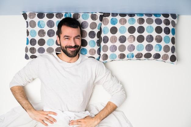 Homme au lit en vue de dessus pose avec les bras à la hanche et souriant
