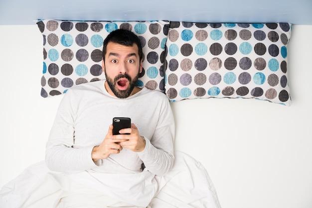 Homme au lit en vue de dessus surpris et envoyant un message