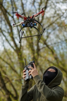Homme au masque actionnant un drone avec télécommande