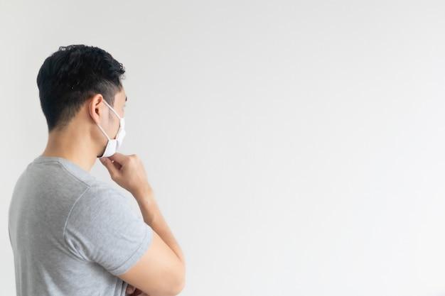 Homme au masque blanc présentant l'espace copie vide sur fond isolé.