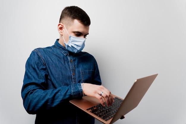 Homme au masque chirurgical à l'aide d'un ordinateur portable.