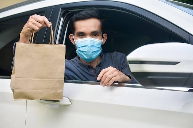 Homme au masque facial assis dans une voiture